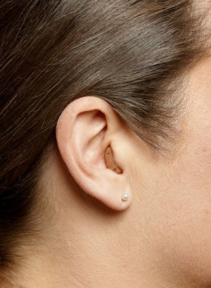 A CIC hearing aid on a woman's ear
