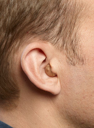 An ITC hearing aid on a man's ear