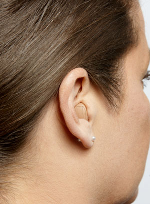 An ITC hearing aid on a woman's ear