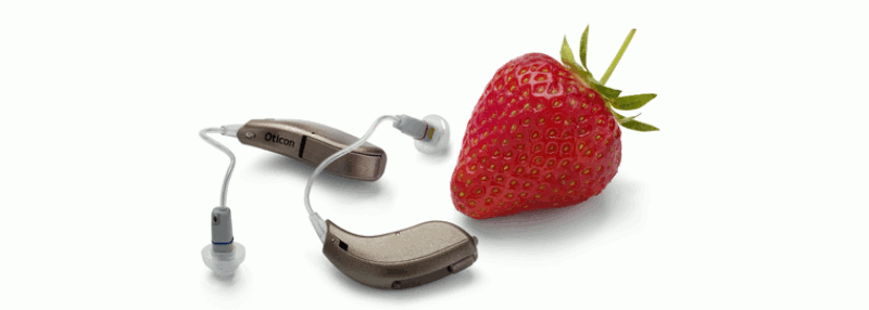 A pair of RITE open dome hearing aids beside a strawberry
