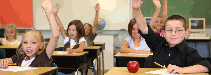 Children seated at desks in a classroom with their arms raised
