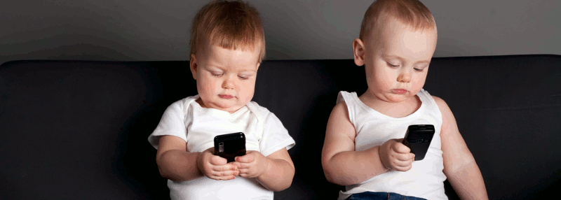 Two babies on a couch playing with mobile phones