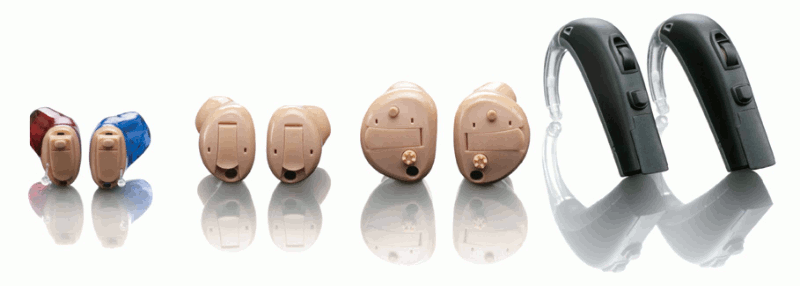 Four pairs of hearing aids on a white background